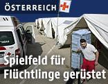 Flüchtlingshelfer in Spielfeld neben Notzelten
