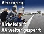 Flüchtlinge sitzen auf Autobahn