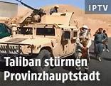 Vermummter Kämpfer neben einem gepanzerten Fahrzeug