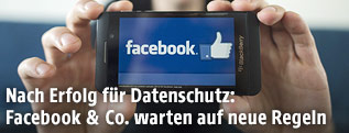 Mann hält Handy mit Facebook-Logo