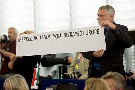 """Europaparlamentarier zeigen Schild mit der Aufschrift """"Merkel, Hollande: Ihr habt Europa betrogen!"""""""