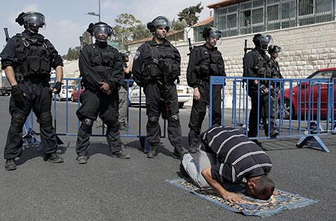 Israelische Soldaten neben einen betenden Mann