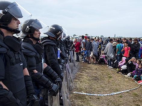 Flüchtlinge und Polizisten in Ungarn