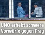 Flüchtlinge an einem Fenster in einem Lager