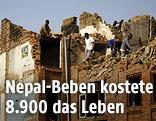 Männer auf einem eingestürzten Haus in Nepal
