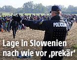 Slowenischer Polizist weist Flüchtlingen den Weg