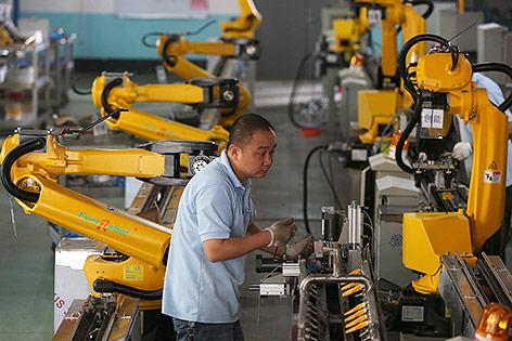 Arbeiter neben Roboterarmen in einer Fabrik