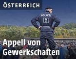 Polizist vor Flüchtlingen