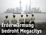 Polizisten stehen vor der Skyline von Schanghai