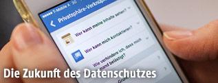 Hand hält Smartphone mit Facebook-Einstellungen auf dem Display