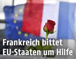 Eine Rose vor einer französischen und EU-Flagge