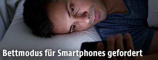 Mann liegt im Bett und schaut auf sein Handy