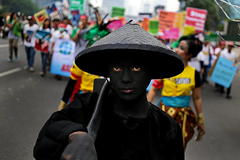 Ein schwarz bemalter Demosntrant führt eine Demonstration in Jakarta, Indonesien an