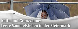 Mann mit Regenschirm hinter Zaun