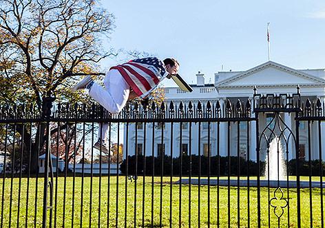 Mann springt über Zaun