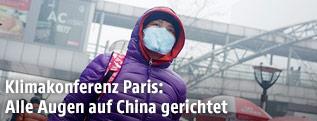 Fußgängerin in Peking mit Mundschutz