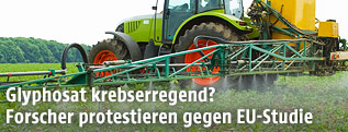 Traktor sprüht Pestizide auf einem Acker
