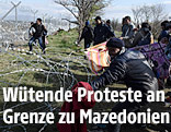 Flüchtlinge versuchen den Grenzzaun zwischen Griechenland und Mazedonien zu entfernen