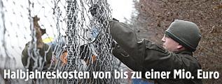 Soldaten errichten einen Grenzzaun