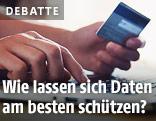 Person hält eine Kreditkarte in der Hand und gibt Daten in einen Laptop ein