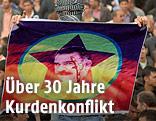Vermummter Kurde mit Öcalan-Transparent