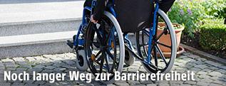 Mann in Rollstul vor Stufen