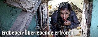 Frau in zerstörtem Haus in Nepal