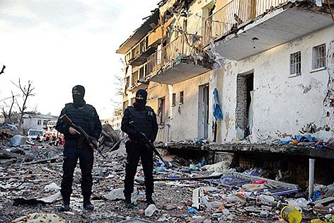 Zwei Polizisten stehen in den Trümmern nach einer Autobombe