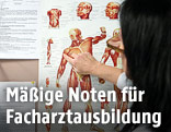 Ärztin deutet auf eine Tafel, die den menschlichen Körper abbildet