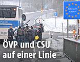 Flüchtlinge neben einem Polizeibus an der bayrisch-österreichischen Grenze