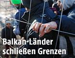Menschen warten an der slowenischen Grenze hinter einem Zaun
