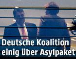 SPD-Chef Sigmar Gabriel und die deutsche Bundeskanzlerin Angela Merkel durch ein Fenster fotografiert