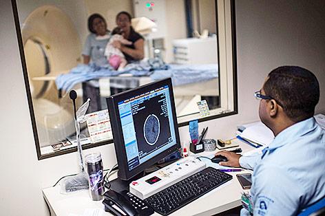 Ein Arzt in Brasilien blickt auf einen Gehirnscan eines Kindes am Monitor