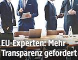 Männer in Anzügen sprechen neben einem Sitzungstisch miteinander