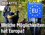 Flüchtlinge stehen neben einem EU-Schild