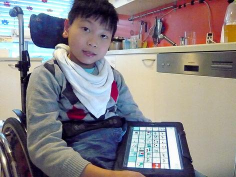 Sprachbehindertes Kind mit seinem Spezial-Tablet