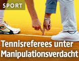 Anonymer Tennis-Spieler und Schiedsrichter deuten auf eine Grundlinie