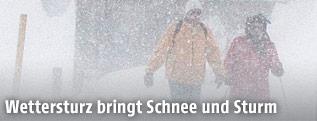 Zwei Menschen gehen bei starken Schneefall