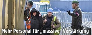 Soldaten führen Flüchtlinge in Spielfeld in ein Aufnahmezelt