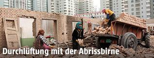 Bauarbeiter reißen ein Gebäude ab