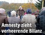 Flüchtlinge hinter einem Zaun