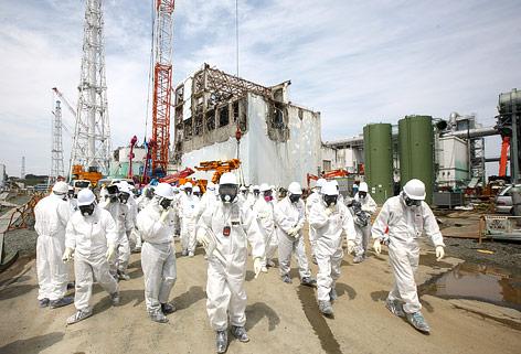 Einsatzkräfte in Spezialanzügen vor dem AKW Fukushima