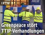Männer mit Schutzwesten und Helmen stören die TTIP-Verhandlungen in Brüssel
