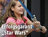 Ein Mädchen hält ein Star-Wars-Lichtschwert