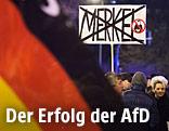 Demonstranten halten ein Schild in welchem der Schriftzug Merkel durchgestrichen ist