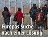 Flüchtlinge gehen an einem zaun entlang