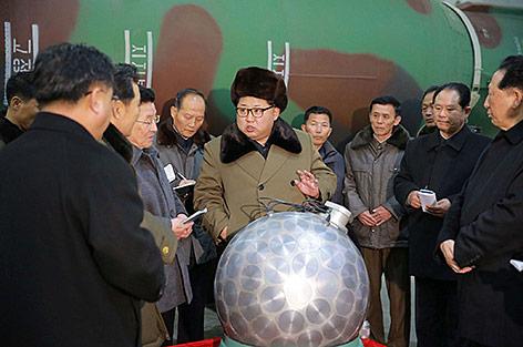 Nordkoreas Diktator Kim Jong Un mit Wissenschafterln neben einem möglichen atomaren Sprengkopf
