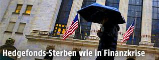 Mann mit Regenschirm geht an der New Yorker Wall Street vorbei