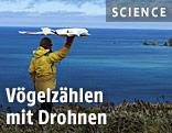 Ein Mann startet eine Drohne an der Küste