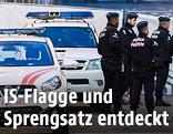 Belgische Polizisten und Einsatzwägen